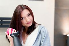 Brunette woman brushing and drying her hair Royalty Free Stock Photo