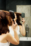 Brunette woman brushing her hair. Royalty Free Stock Image