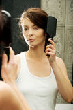 Brunette woman brushing her hair. Royalty Free Stock Photo
