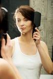Brunette woman brushing her hair. Royalty Free Stock Photo