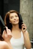 Brunette woman brushing her hair. Stock Images