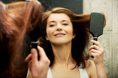 Brunette woman brushing her hair. Royalty Free Stock Photos