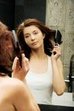 Brunette woman brushing her hair. Royalty Free Stock Image