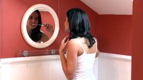Brunette woman brushing her teeth