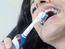 Brunette woman brushing teeth with  electric tooth. Brunette woman brushing teeth with an electric toothbrush Stock Photos