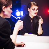 Brunette woman in business costume lighting a cigarette in front of the mirror with color backlight Royalty Free Stock Photography