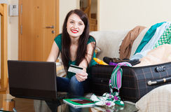 Brunette woman buying hotel or ticket. At internet using laptop and card Royalty Free Stock Image