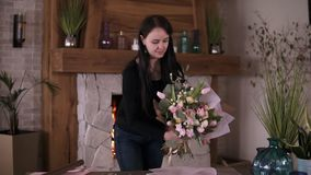 Brunette woman in casual floral artist, florist wraps flowers - pink roses in gift paper at workshop, home studio. Floristry, handmade and small business stock footage
