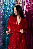 Brunette woman celebrating, having fun at the party. Portrait of a happy smiling girl in a stylish glamorous shiny red  dress stock photo