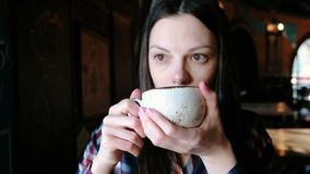 Brunette woman in checkered shirt drinking tea from a large cup. Tired woman have a tea. Brunette woman in checkered shirt drinking tea from a large cup. Tired stock video