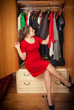 Brunette woman choosing dresses in big wardrobe Stock Photos