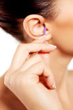 Brunette woman cleaning her ear. Royalty Free Stock Images