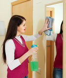 Brunette woman cleaning  mirror Royalty Free Stock Image