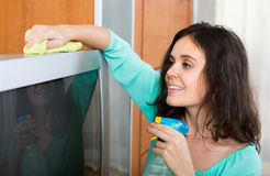 Brunette woman cleaning TV. Smiling young brunette woman cleaning TV with rag at home Stock Image