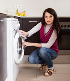 Brunette woman cleaning washing machine Royalty Free Stock Photos