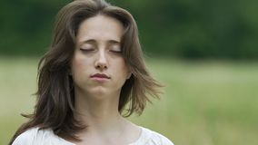 Brunette woman with closed eyes raises head and moves her hair deep relaxation. Stock footage stock footage