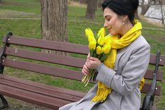 Brunette woman in coats with yellow tulips. 1 Royalty Free Stock Images