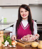 Brunette woman cooking with meat Royalty Free Stock Photography