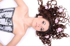 Brunette woman in corset lying with flowers Stock Images