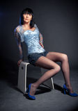 Brunette woman in corset posing on chair Stock Photo