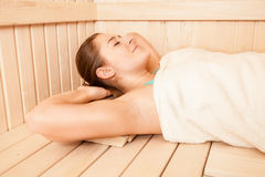 Brunette woman covered in towel lying at sauna Stock Photo