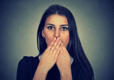 Brunette woman covers her mouth with hands. Brunette young woman covers her mouth with hands Stock Photos