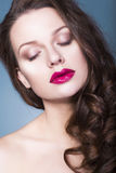 Brunette woman with creative make up violet eye shadows full red lips, blue eyes and curly hair with her hand on her face. Beautiful brunette woman with creative stock photo