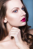 Brunette woman with creative make up violet eye shadows full red lips, blue eyes and curly hair with her hand on her face Royalty Free Stock Photography