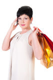 Brunette woman in creme dress with shopping bags posing Stock Photo