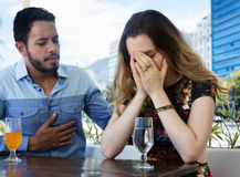Brunette woman crying after relationship difficulties with husband. Brunette women crying after relationship difficulties with husband in a bar in the summer in stock photography
