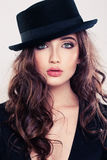 Brunette Woman with Curly Hair and Black Hat Stock Photo