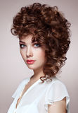 Brunette woman with curly and shiny hair. Beautiful model with wavy hairstyle. Fashion photo Royalty Free Stock Photography