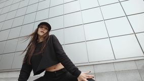 Brunette woman dancing, perform modern hip-hop dance contemporary freestyle in the street, urban