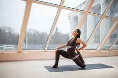 Brunette woman in a dark jumpsuit standing in Horse rider exercise, anjaneyasana pose in front of large windows. working out, full. Length, wearing sportswear stock images