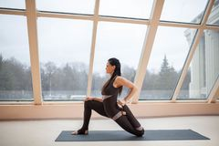 Brunette woman in a dark jumpsuit standing in Horse rider exercise, anjaneyasana pose in front of large windows. working out, full. Length, wearing sportswear royalty free stock photo