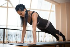 Brunette woman in a dark jumpsuit standing in Push ups, press ups exercise, phalankasana, Plank pose in front of large windows. wo. Rking out, full length Royalty Free Stock Images