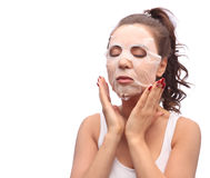 Brunette woman doing facial mask sheet. Beauty and Skin Care Concept. Girl applying mask to her face, studio shot. Brunette woman doing facial mask sheet. Beauty royalty free stock photo