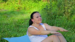 Brunette woman doing press exercises on the lake in the morning. Overall plan stock video