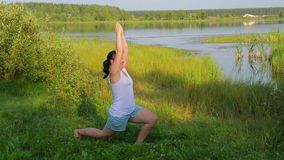 Brunette woman doing yoga in the pose of the hero on the lake in the morning. Overall plan stock footage