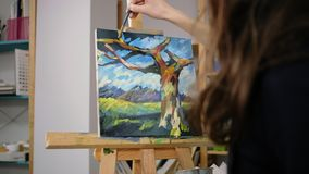 Brunette woman is drawing sky on abstract picture in art-therapy class, closeup. Young artist woman is depicting blue sky on landscape in art studio. She is stock video footage