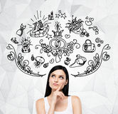 Brunette woman is dreaming about sopping. Shopping icons are flying in the air. Royalty Free Stock Photo