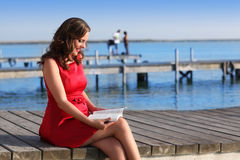Brunette woman dress in red reading a book Royalty Free Stock Image