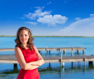 Brunette woman dress in red smiling on a lake Royalty Free Stock Photos