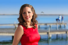 Brunette woman dress in red smiling on a lake Royalty Free Stock Image