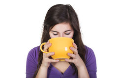 Brunette woman drinking beverage from a big yellow cup isolated on white Stock Image