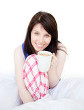 Brunette woman drinking coffee sitting on bed Royalty Free Stock Photography