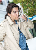 Brunette woman drinking a glass of water Stock Photos