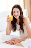 Brunette woman drinking orange juice on bed Stock Photos