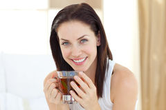 Brunette woman drinking tea. Sitting on her bed Royalty Free Stock Photo