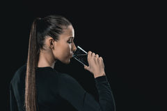 Brunette woman drinking water isolated on black, healthy living concept. Young brunette woman drinking water isolated on black, healthy living concept Royalty Free Stock Photography